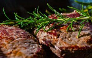 Steaks und anderes Fleisch in einer Gusseisernen Pfanne anbraten